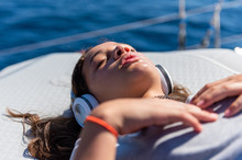 Cute Young Girl Is Listening To Her Favorite Music While Laying On A Yacht