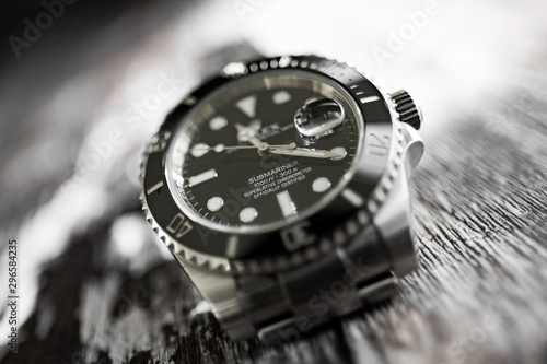 Photographie Close-up, abstract and shallow focus view of an iconic, swiss-made men's automatic divers watch showing the ceramic bezel and famous cyclops date lens