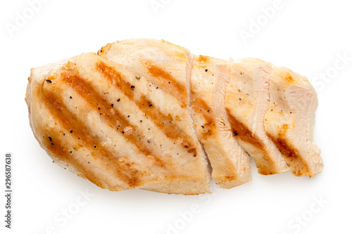 Fototapeta  Partially sliced grilled chicken breast with grill marks, ground black pepper and salt isolated on white