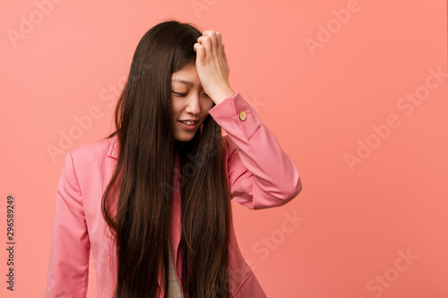 Fényképezés  Young business chinese woman wearing pink suit forgetting something, slapping forehead with palm and closing eyes