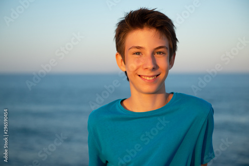 Montage in der Fensternische Blau türkis Handsome young boy at beach. Beautiful calm smiling teen boy at Mediterranean sea coast. Travel, summer vacation, tourism, teenage lifestyle.