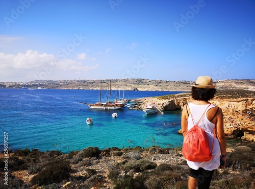 Foto tourist from behind blue lagoon in comino, Malta
