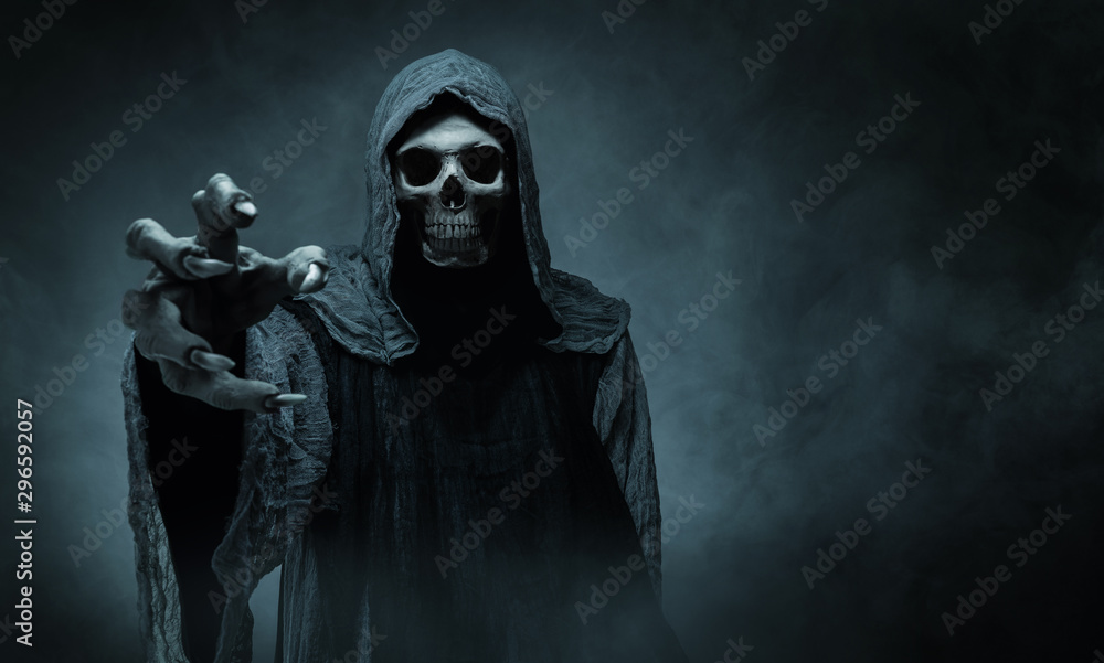 Fototapeta Grim reaper reaching towards the camera over dark background with copy space