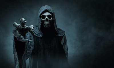 FototapetaGrim reaper reaching towards the camera over dark background with copy space