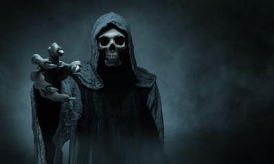 Fototapeta na wymiar Grim reaper reaching towards the camera over dark background with copy space