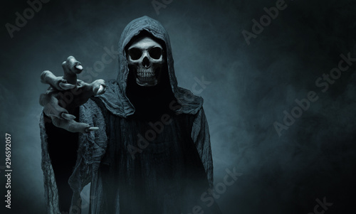 Grim reaper reaching towards the camera over dark background with copy space - 296592057