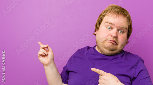Fotografie, Obraz  Young authentic redhead fat man shocked pointing with index fingers to a copy space