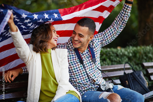 Happy young couple of tourists with a USA flag Fotobehang