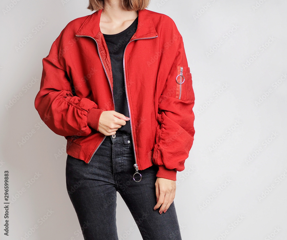 Fototapeta Young woman wearing bold outfit with black sweater, red bomber jacket and black high-waisted jeans isolated on light grey background. Copy space