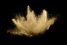 Golden Powder Explosion On Black Background. Freeze Motion.