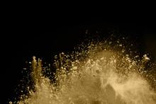Golden Powder Explosion On Black Background. Freeze Motion.