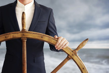 Businessman Holding Ship Wheel And Navigates In Storm.