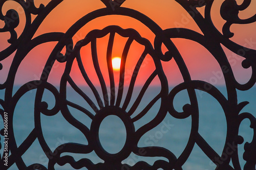 A beautiful Sunset is visible through a cast-iron openwork lattice Wallpaper Mural