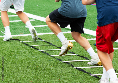 Three athletes in cleats doing ladder foot drills on turf field Canvas Print
