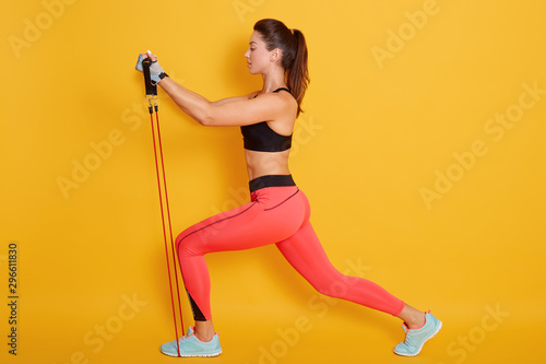 Carta da parati  Full length profile view of young brunette woman wearing stylish exercise clothing and stretching in leg lunge position with expander, posing isolated over yellow studio background