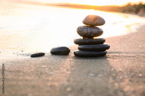 Photo sur Toile Zen pierres a sable Dark stones on sand near sea at sunset, space for text. Zen concept