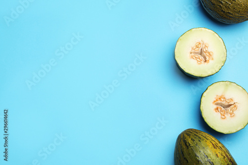 Ripe tasty melons on blue background, flat lay. Space for text Fototapeta