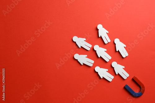 Photo Magnet attracting paper people on red background, flat lay