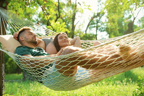 Fototapeta Young couple resting in comfortable hammock at green garden obraz