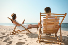 Young Woman Reading Book And Man Relaxing In Deck Chairs On Beach Near Sea