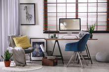 Comfortable Workplace Near Window With Horizontal Blinds In Room