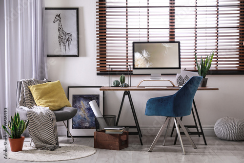 Obraz Comfortable workplace near window with horizontal blinds in room - fototapety do salonu