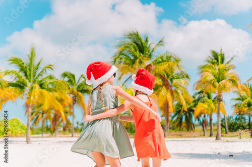 Poster Palmier Little adorable girls in Santa hats during beach Christmas vacation having fun together