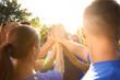 Leinwandbild Motiv Group of volunteers joining hands together outdoors on sunny day