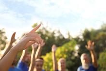 Woman At Volunteers Meeting, Focus On Hand. Group Of People Outdoors