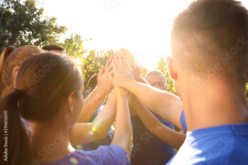 Obraz Group of volunteers joining hands together outdoors on sunny day - fototapety do salonu