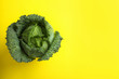 canvas print picture - Fresh savoy cabbage on yellow background, top view. Space for text