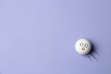Golf ball with funny face flying on lilac background - creative image. Top view