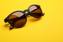 Stylish Sunglasses On Yellow Background. Fashionable Accessory