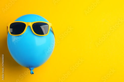 Fotografía  Balloon with sunglasses on yellow background, top view