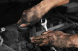 canvas print picture - Dirty mechanic fixing car, closeup of hands