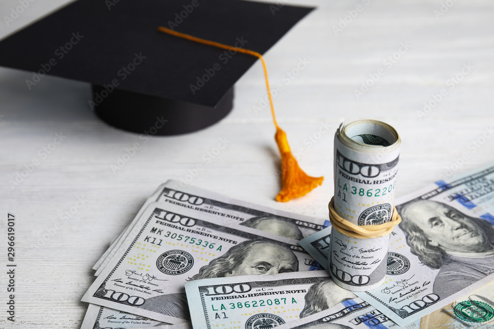 Fototapeta Dollar banknotes and student graduation hat on white wooden background. Tuition fees concept