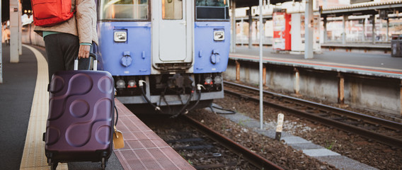 Traveller woman carrying suitcase at train transport destination.