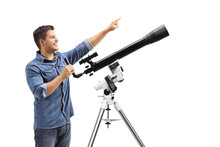 Youn Man Standing Next To A Telescope And Pointing Up