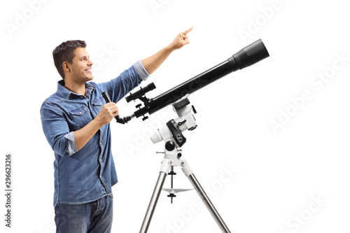 Fototapeta Youn man standing next to a telescope and pointing up obraz