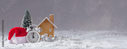 Christmas alarm clock, Santa Claus hat, small wooden toy cottage and fir-tree with balls, banner, snowflakes effect