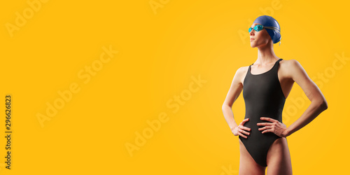 Canvas Print Young female swimmer portrait of half body in black swimsuit with goggle and swimming hat