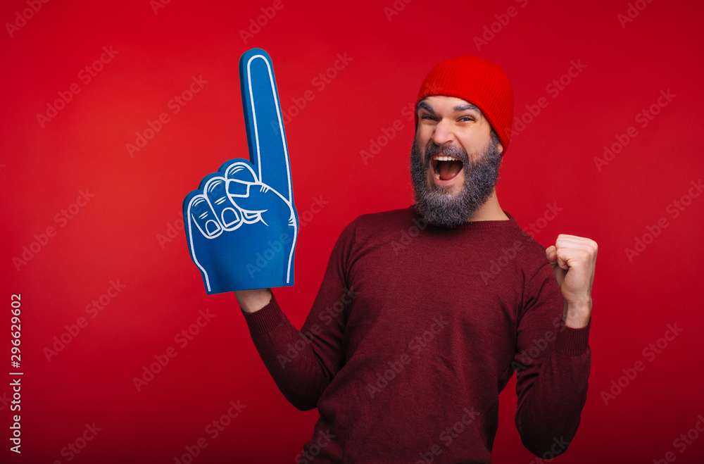 Fototapeta Amazed bearded hipster man standing over red background and celebrating success with fan finger glove