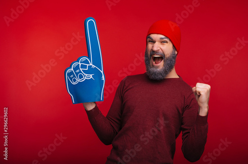 Amazed bearded hipster man standing over red background and celebrating success with fan finger glove
