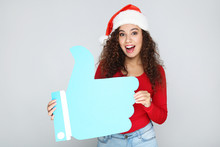 Beautiful American Woman Wearing Santa Hat And Holding Paper Thumb Up On Grey Background