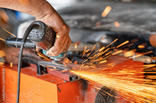 Fototapeta  Cutting industrial metal with grinder. Sparks while grinding iron