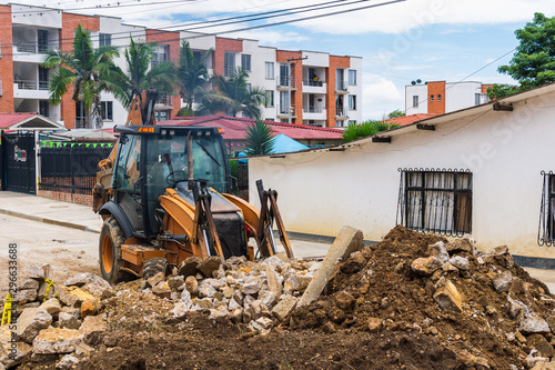 Backhoe in downtown making arrangements Wallpaper Mural