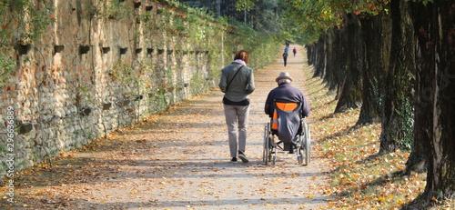 Photo Accompagnatrice con disabile nel parco in autunno