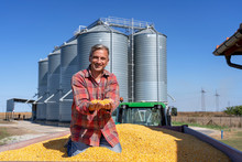Smiling Farmer Sitting In Tractor Trailer Full Of Corn Seeds In Front Of Farm Grain Bins
