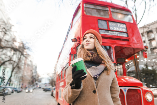 A street photo of a young woman in a coat and cap walking down the street with a cup of coffee in her hand and looking away Wallpaper Mural