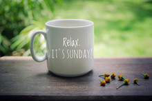 Sunday Mug Of Coffee Concept. Morning White Coffee With Text On It - Relax. It Is Sunday, And Yellow Little Flowers Arrangement On Natural Wooden Table. Green Garden Bokeh Background.